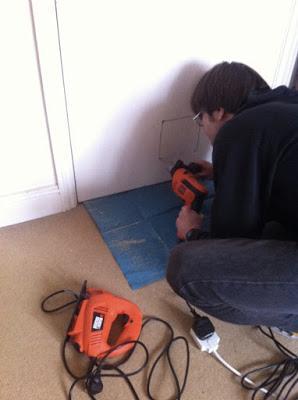 電動ジグソーを使ってドアに四角い穴を開けました